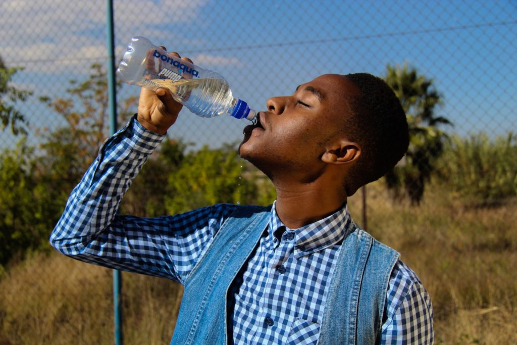 African young man drinking a bottle of water